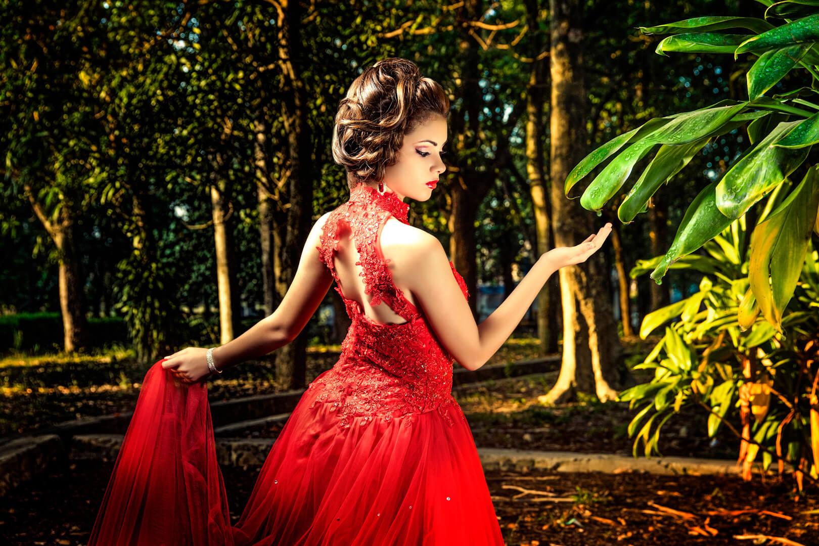 quinceañera de espaldas en vestido de color rojo mirando como cae una gota de agua en su mano