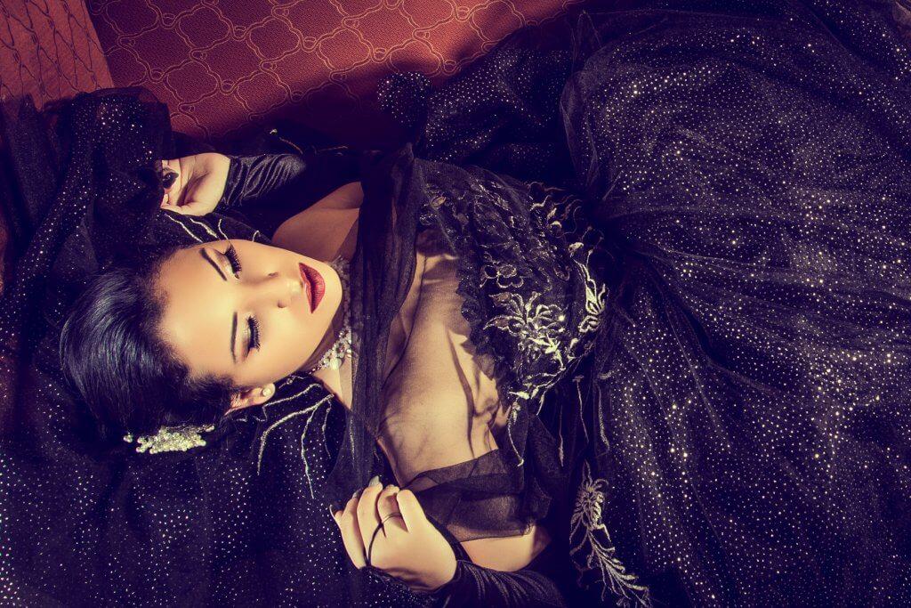 fotografia de una quinceañera en cuba usando un traje de color negro acostada en sofá