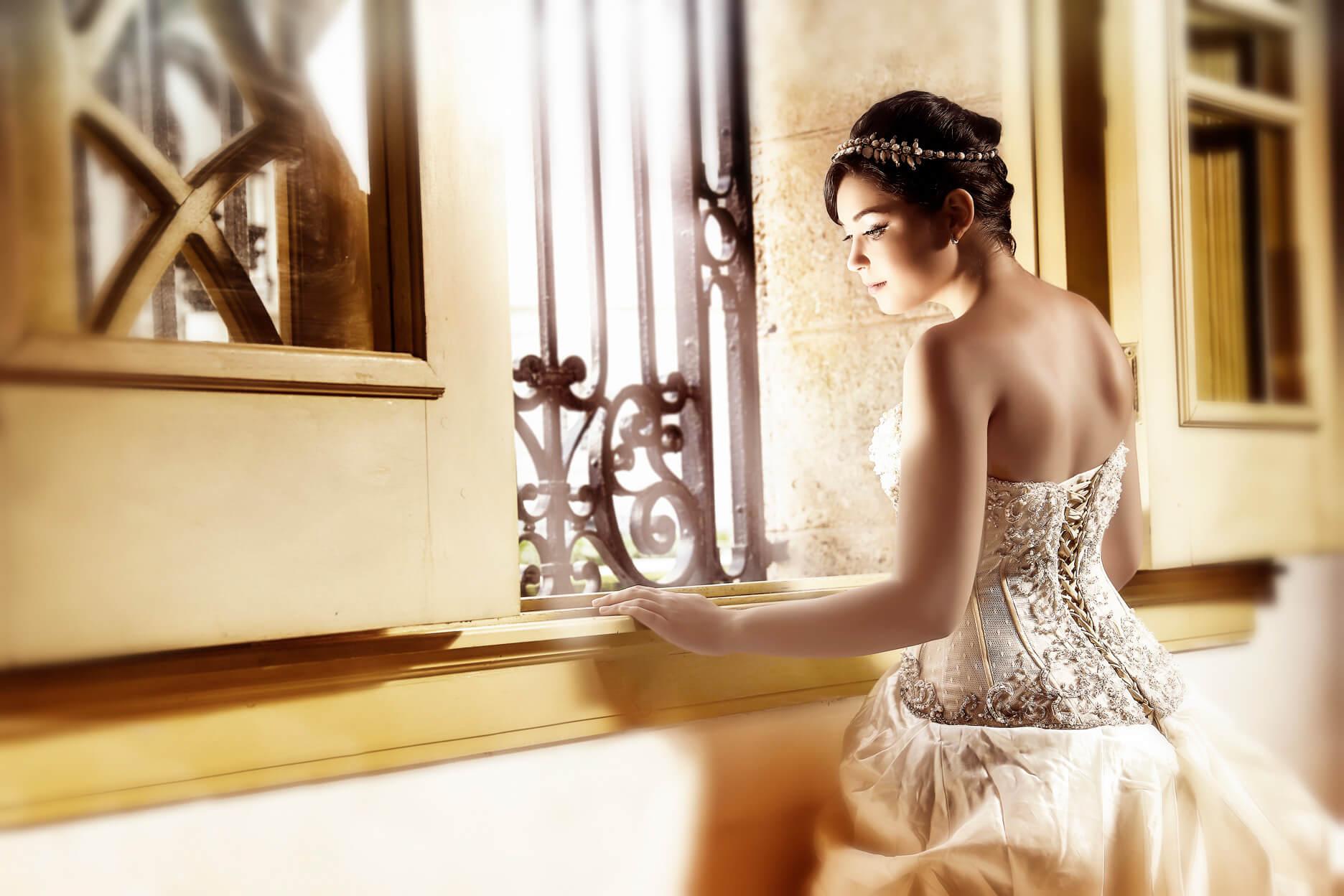 fotografia por Estudios Mahe de una quinceañera posando frenta a una ventana usando un vestido blanco