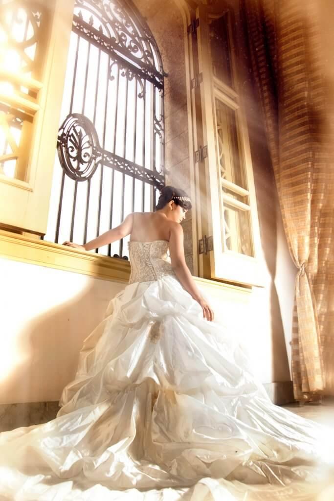 quinceañera apoyada a ventana usando un traje blaco