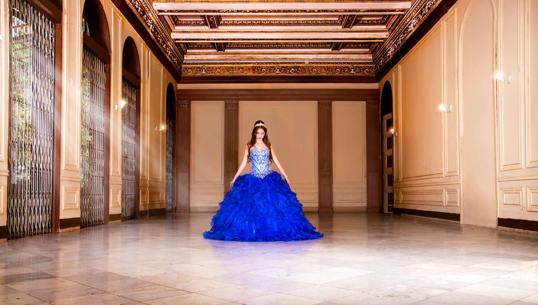 quinceañera en traje de color azul posando en el centro de un salón