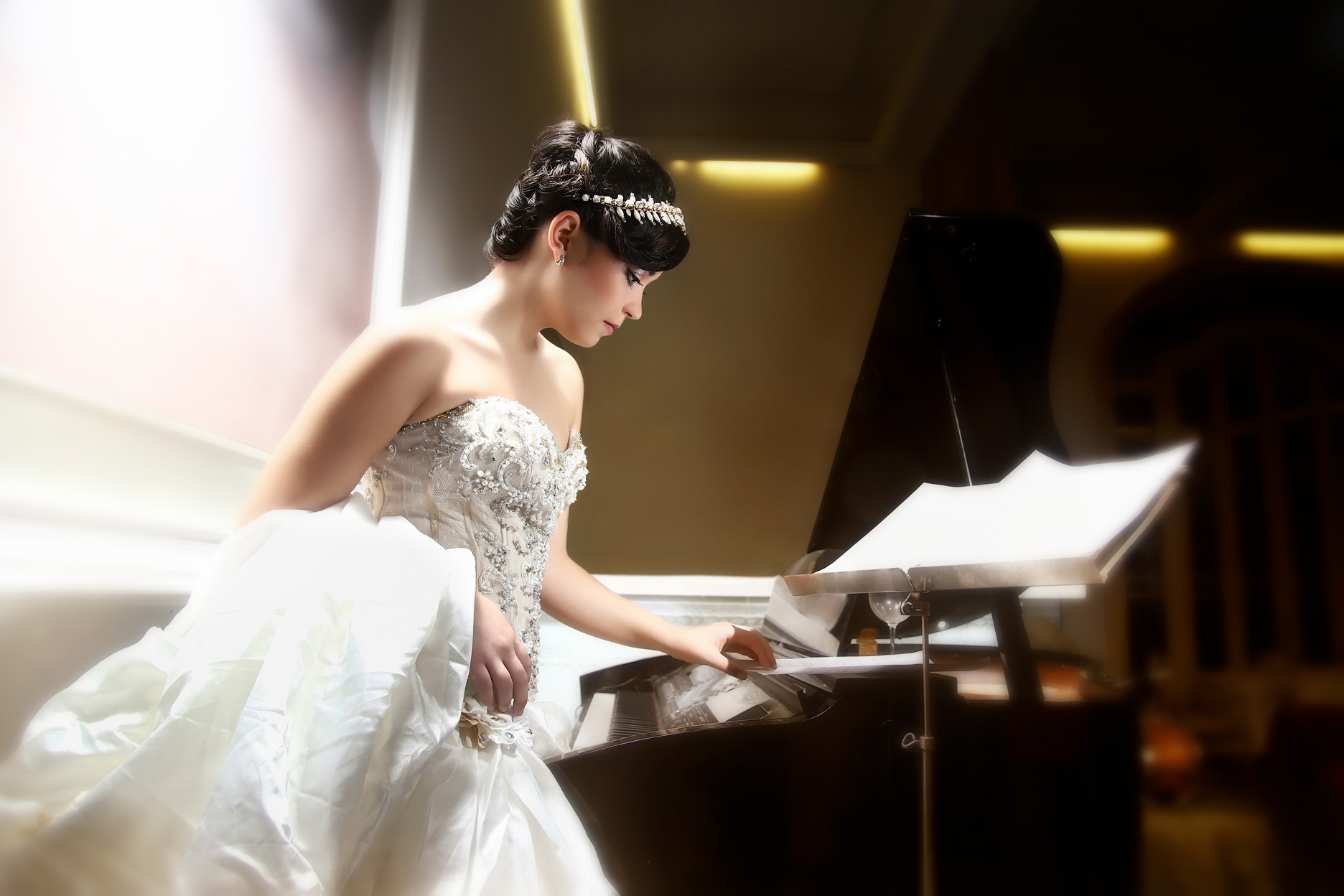 quinceañera fotgrafiada por Estudios Mahe usando vestido blanco frente a un piano