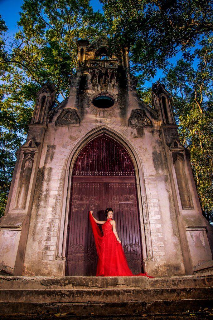 quinceañera usando vestido rojo posando en la puerta de una pequeña iglesia