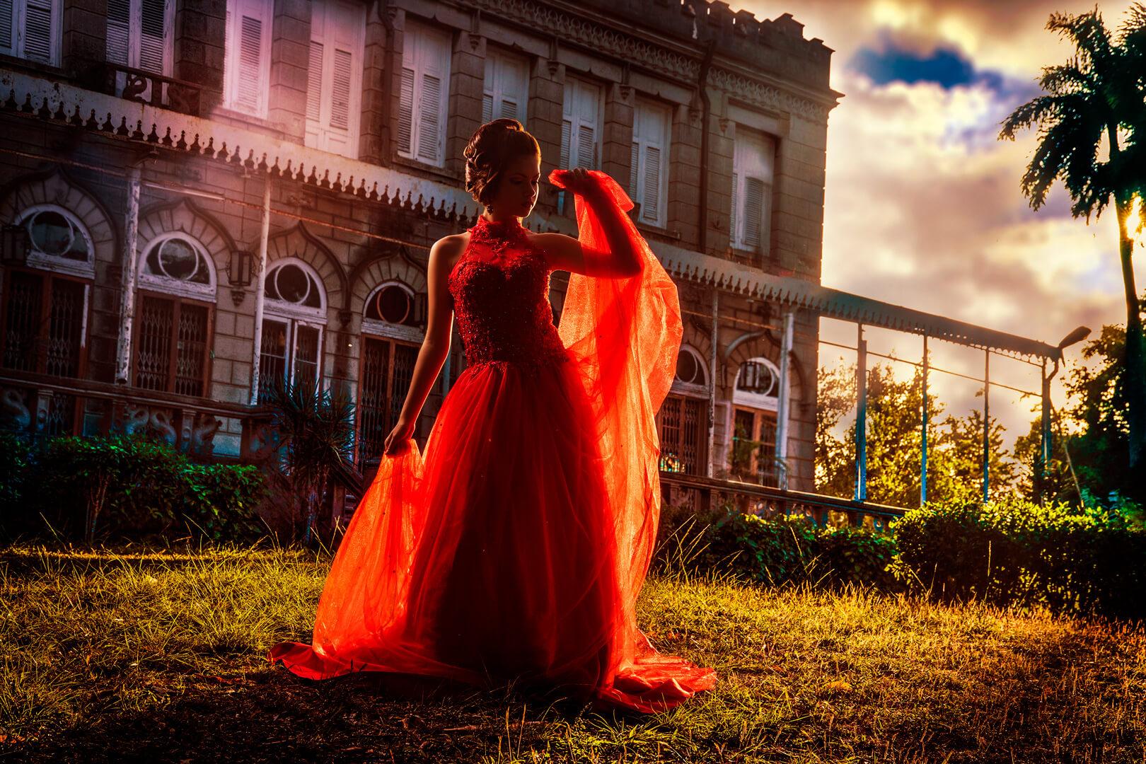 quinceañera posando a contraluz usando un vestido rojo