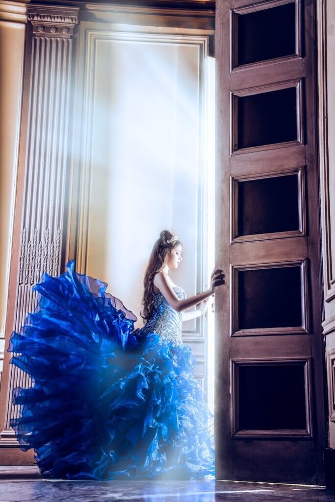 quinceañera fotografiada por Estudios Mahe vistiendo un traje azul abriendo una enorme puerta