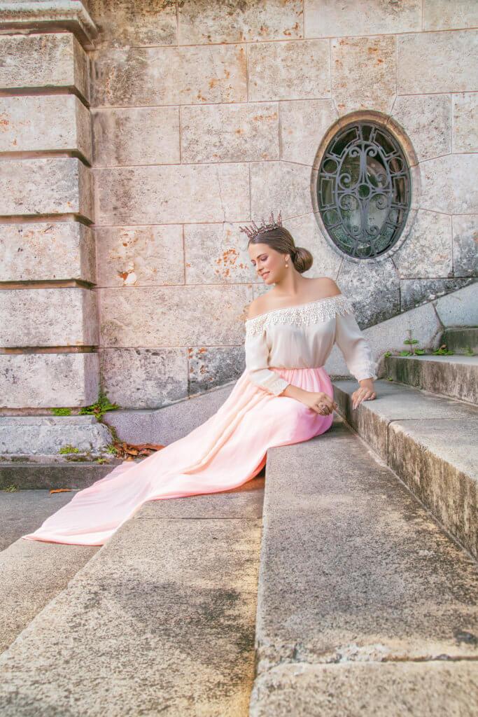 foto quinceañera en exterior posando sentada usando vestido rosa