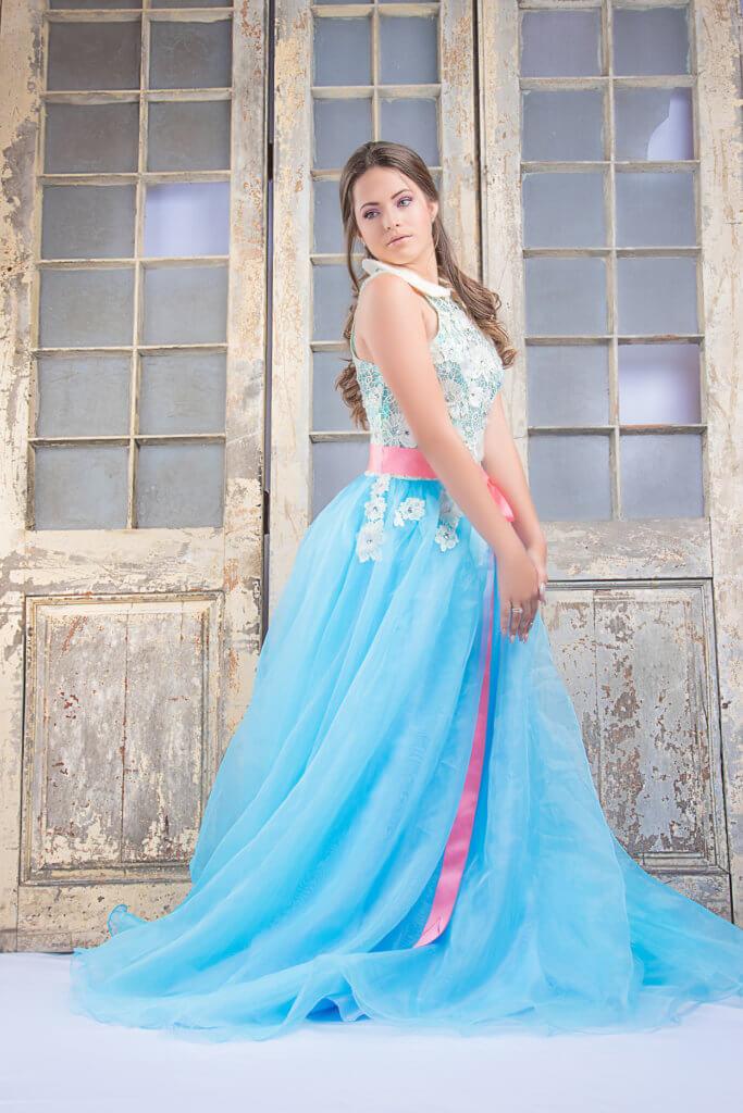 foto quinceañera en traje azul con puerta de fondo