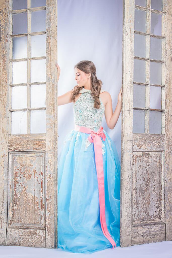 foto quinceañera en traje azul y cinta rosada con puerta de fondo